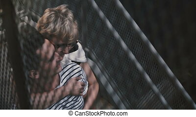 Beautiful Hispanic man and Caucasian woman standing and hugging on metallic city street stairs, view through fence. Multiethnic romantic couple sharing time of togetherness, on a romantic date.