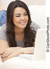 Beautiful Hispanic Woman Laying on Sofa Using Laptop Computer