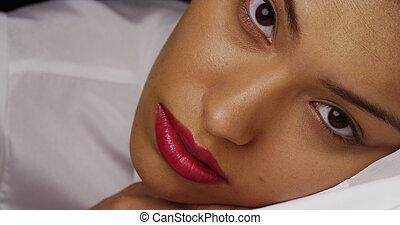 Beautiful Hispanic woman lying down and looking at camera