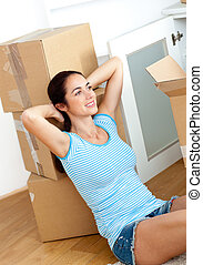 Beautiful hispanic woman relaxing at the middle of boxes on the floor in her new house