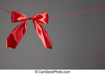Beautiful holidays red satin bow on gray