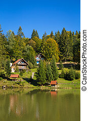 beautiful houses by the lake in the autumn forest