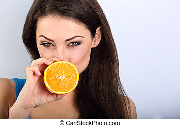 Beautiful humor emotional brunette woman with healthy skin holding fresh orange fruits near the eyes and looking happy on blue background with empty copy space. Closeup portrait