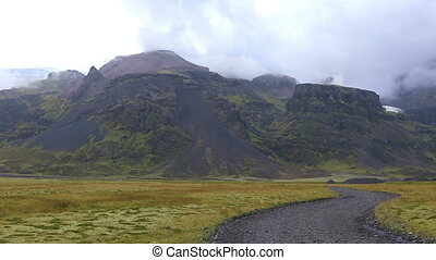 Beautiful Icelandic landscape with mountains, dirt road and...