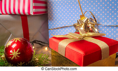 Beautiful image for winter holidays and celebrations. Gift boxes, glowing lights and Christmas decoration on wooden background