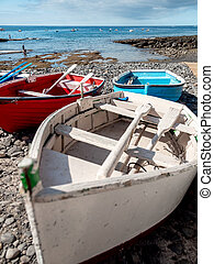 Beautiful image of rocky ocean shore and old wooden rowing boats at bright sunny day