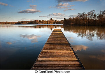 Beautiful image of sunset landscape of wooden fishing jetty on calm lake with clear reflections