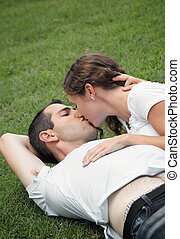 beautiful image of young lovers kissing in the park