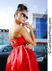 beautiful independent brunette in sunglasses and red dress