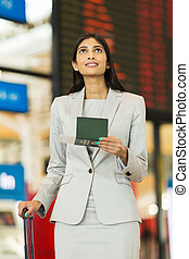 indian business traveller checking flight information at airport