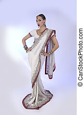 Beautiful Indian Woman in Traditional Sari Clothing with Bridal Makeup and oriental jewelry.