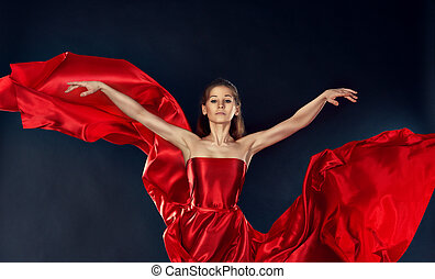 beautiful inspirational woman dancing in a theatrical red silk dress flying