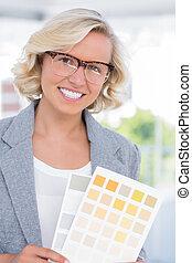 Beautiful interior designer holding up colour samples in...