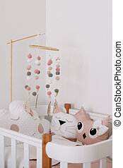 Beautiful interior of baby room. White crib with pillows and pink blanket in baby room. pink bedding on bed against white wall