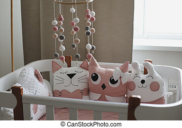 Beautiful interior of baby room with a crib. White crib with pillows and pink blanket in baby room. pastel pink bedding