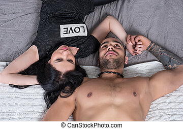 Beautiful international couple of man with bare chest and brunette woman lying on the bed