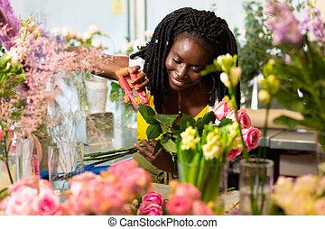 Beautiful international florist taking care of flowers