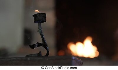 Beautiful iron rose at a hearth with fire in a blacksmith...
