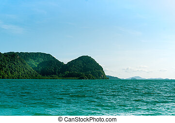 beautiful island with tree covered mountains and blue water