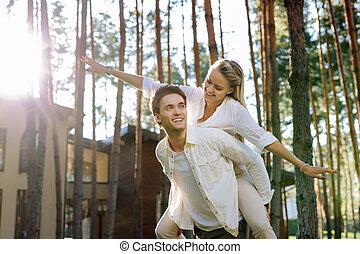 Beautiful joyful woman being held by her husband