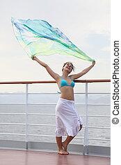beautiful joyful woman with kerchief standing on deck of cruise ship.