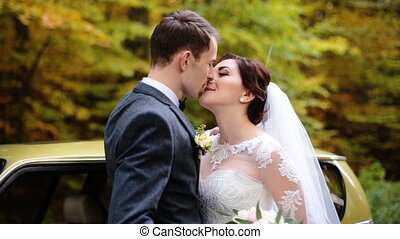 Beautiful just married couple kissing each others in front...