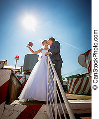 just married couple kissing on the roof top of skyscraper
