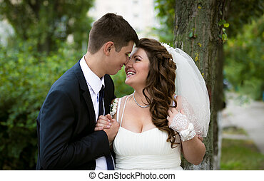 just married couple looking at each other eyes at park -...