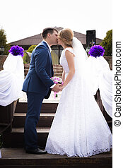just married couple standing face to face and kissing
