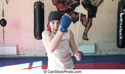 Beautiful Kickboxing woman training punching bag in fitness...