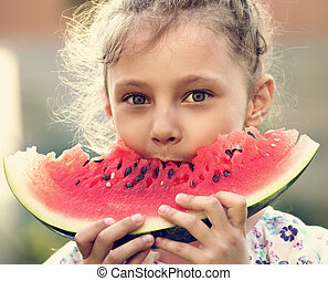 Beautiful kid girl eating big red tasty watermelon with cute look on summer day green glass background. Closeup portrait. Toned