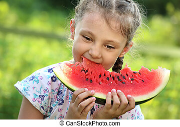 Beautiful kid girl eating big red watermelon with fun emotional look on summer day green glass background. Closeup portrait