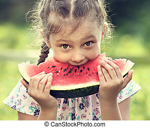 Beautiful kid girl eating big red watermelon with fun humor look on summer day green glass background. Closeup toned portrait