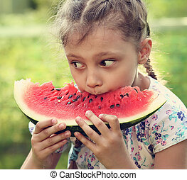 Beautiful kid girl eating big red watermelon with fun look on summer day green glass background. Closeup toned potrait