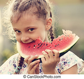 Beautiful kid girl eating big red watermelon with fun look on summer day green glass background. Closeup fun cute potrait. Toned