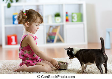 Beautiful kid girl feeding her dog in the living room