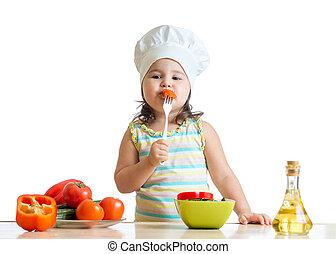 kid girl in cook hat eating vegetables