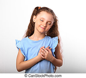 Beautiful kid girl in love holding herself chest and heart two hands with enjoying smiling face and thinking about on white background