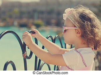 Beautiful kid girl in sun glasses looking on the blue sea. Vintage portrait
