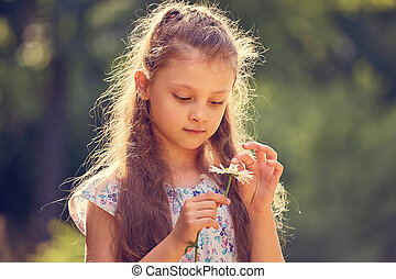 Beautiful kid girl looking on chamomile flower on nature summer green background. Closeup portrait