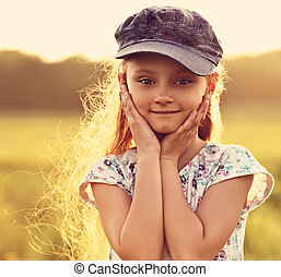 Beautiful kid girl with long hair in fashion blue cap smiling outdoors summer sunny green background. Closeup toned color portrait
