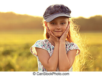 Beautiful kid girl with long hair in fashion blue cap smiling outdoors summer sunny green background. Closeup bright portrait