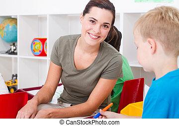 beautiful kindergarten teacher in classroom with kids