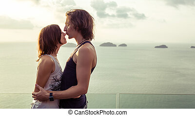 Beautiful kissing couple on the tropical sunset background