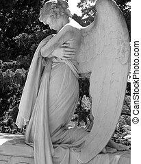 Beautiful kneeling angelic statue on historic cemetery of Staglieno