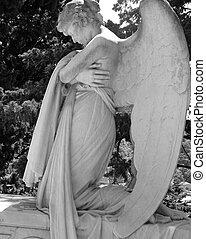 Beautiful kneeling angelic statue on historic cemetery of Staglieno