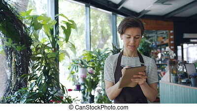 Beautiful lady counting plants writing data in notebook ...