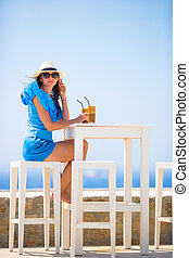Beautiful lady drinking cold coffee enjoying sea view....