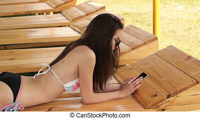 beautiful lady in a bathing suit lies in the beach and looks to your phone