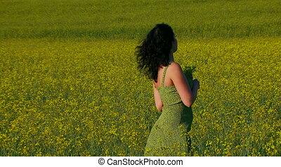 Beautiful lady in green dress is posing on the field of Raps.
